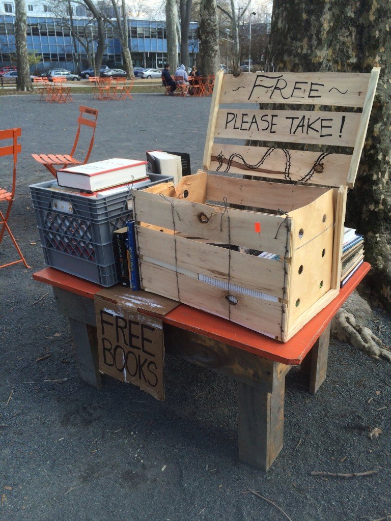 """Color photograph of two crates filled with books, a sign reading """"Free Books"""", some orange metal chairs as well as trees in a gravel section of a park in West Philly."""